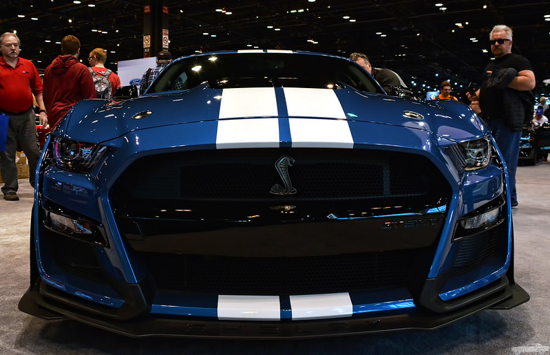 The front of a blue 2020 Ford Mustang Shelby GT500 with white racing stripes